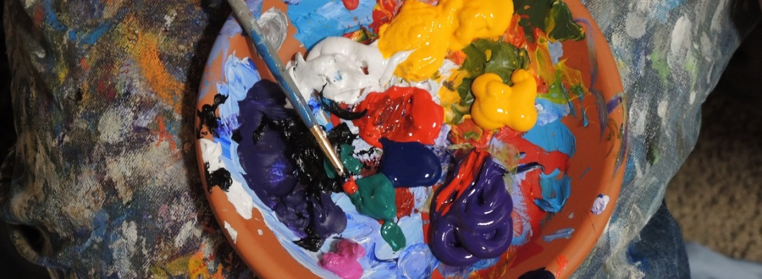Several colors of paint and a paint brush in a dish on a paint splattered drop cloth