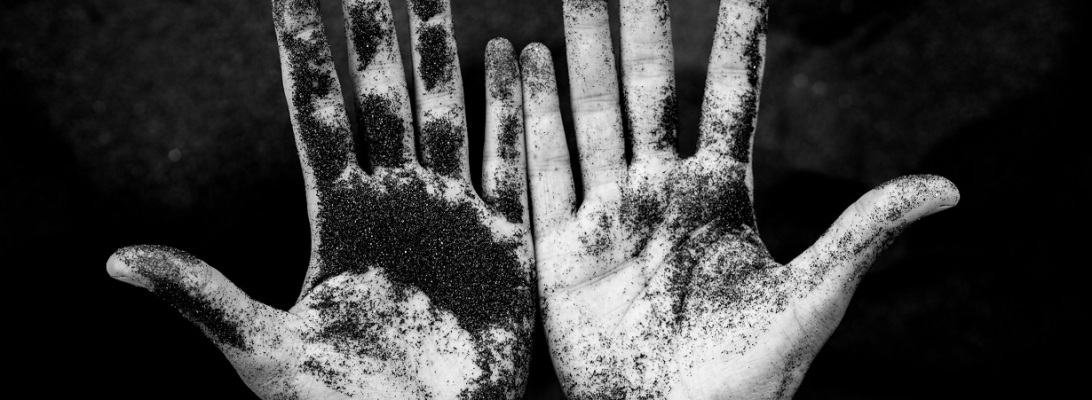 Black and white photo of white hands with black sand on them