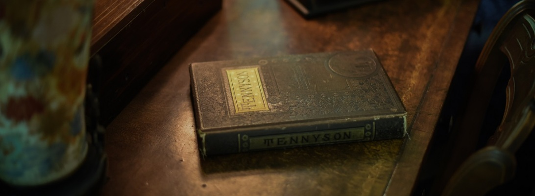 Book of Tennyson poems on old wooden dresser