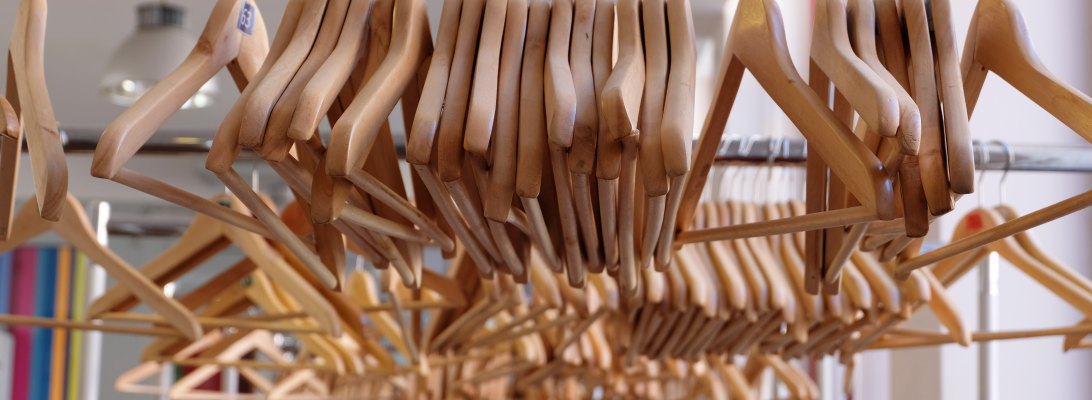 Wooden hangers on a rack at a clothing store