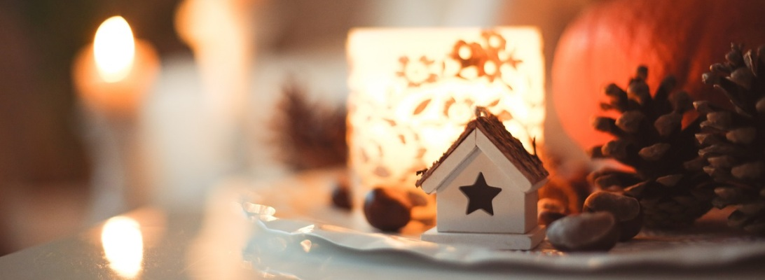 Candles lit behind a small white house ornament and a pinecone on a table