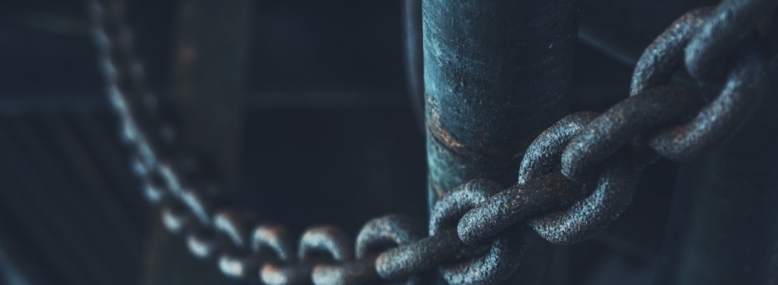 Close up of metal chain hung across a pillar in a dark room
